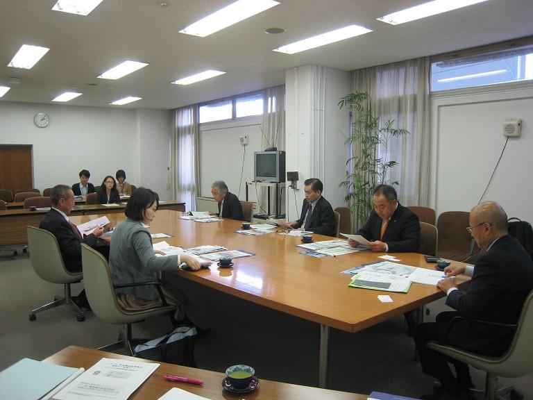 担当課長(奥)から話を聞く委員会の6人(手前)=10月23日、尼崎市役所