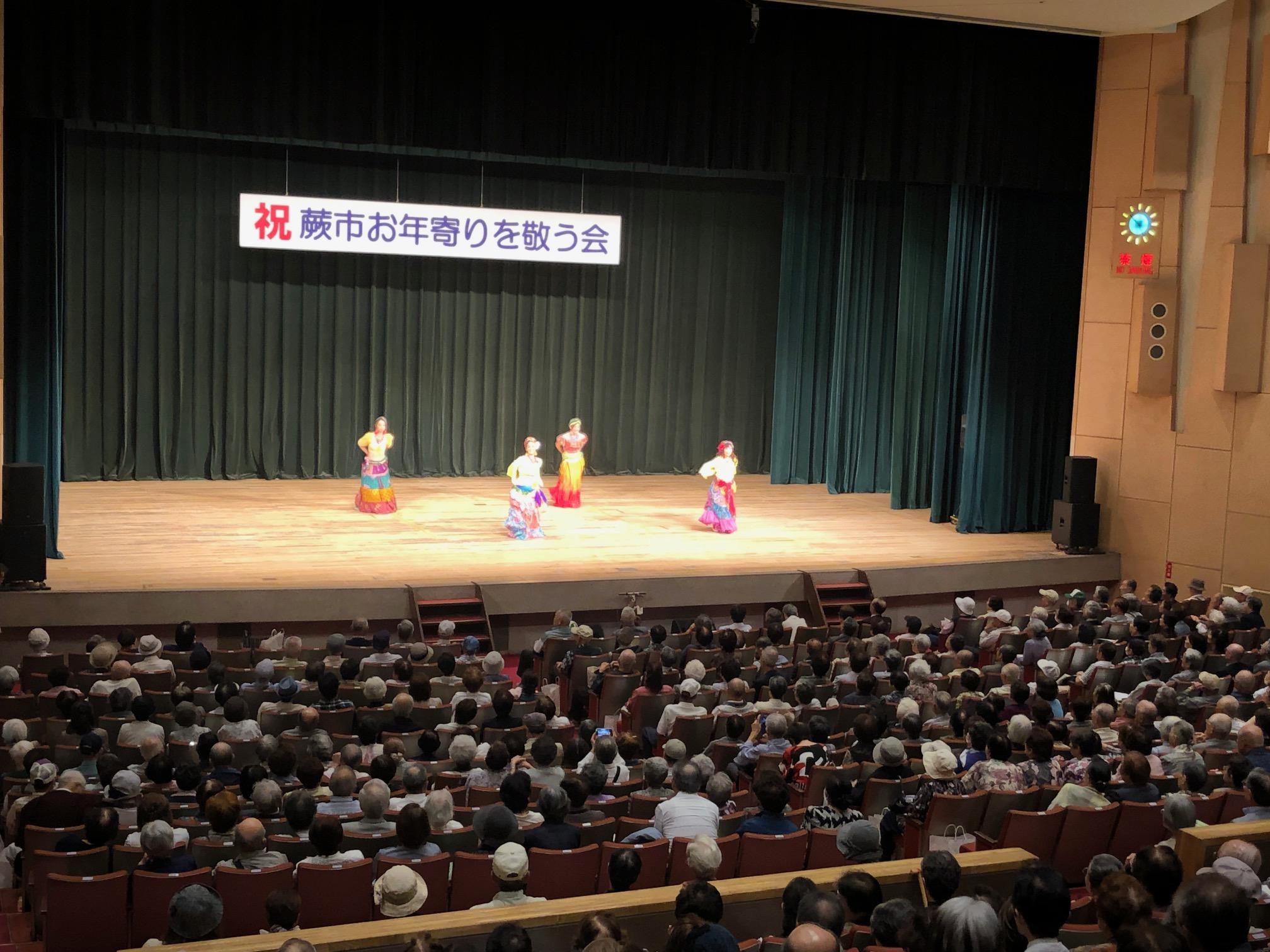 ↑演芸の部で楽しむ会場いっぱいの参加者